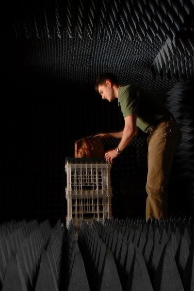 Engineering grad student Glen Garner positions a rock for acoustic probing in the anechoic chamber in Monteith Hall. Photo by Roger Winstead