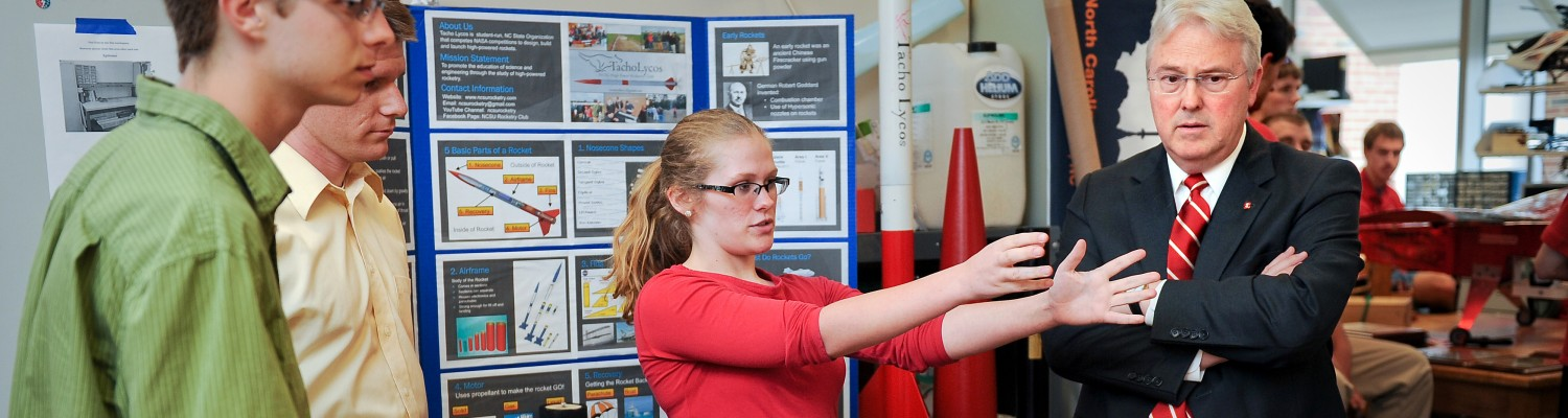 Alyssa Doman, a member of the NC State University Rocketry Team, shows Chancellor Randy Woodson examples of the club's work.